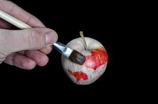 Une main peint une pomme en rouge sur un fond noir